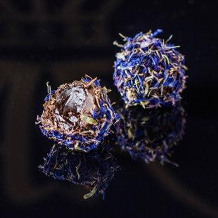 Plūškoka krēma trifele pārklāta ar rudzupuķu ziedlapiņām