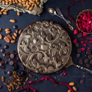 Tumšās šokolādes torte pildīta ar mandelēm, plūmēm, aprikozēm un rozīnēm
